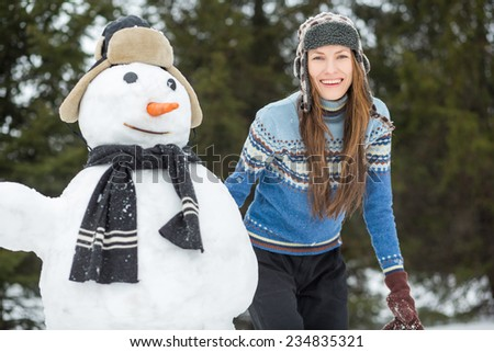 Outdoor portrait of happy winter woman with snowman. focus on woman - stock photo