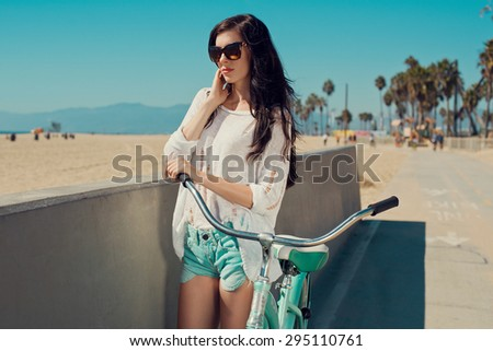 Outdoor portrait of happy woman biking in city park. Joy and happiness. Young woman in shorts, sunglasses on holidays. Venice, Los Angeles. - stock photo