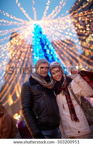Outdoor portrait of happy young couple doing christmas shopping at christmas fair.