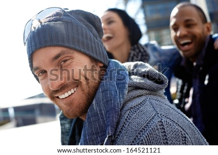 Outdoor portrait of happy young man wearing scarf and smiling at camera.