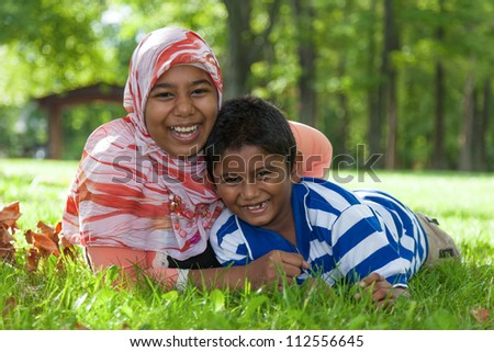 Outdoor portrait of indian brother and sister - stock photo
