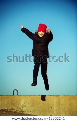 Outdoor portrait of jumping cheerful little girl - stock photo