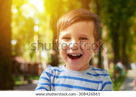 outdoor portrait of laughing pretty boy - stock photo