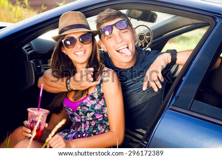Outdoor portrait of laughing smiley couple,shows funny faces together,couple in sunglasses,funny face,funky,fancy,emotional people,hikers,funny couple,romantic date,road trip,friends having fun,trip - stock photo