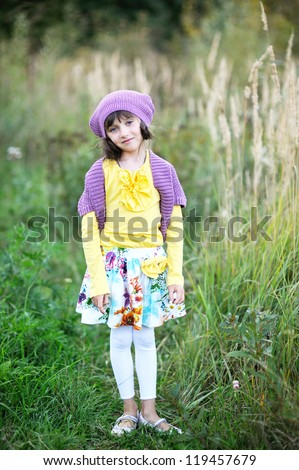 Outdoor portrait of little blue-eyed girl in violet hat standing in forest park