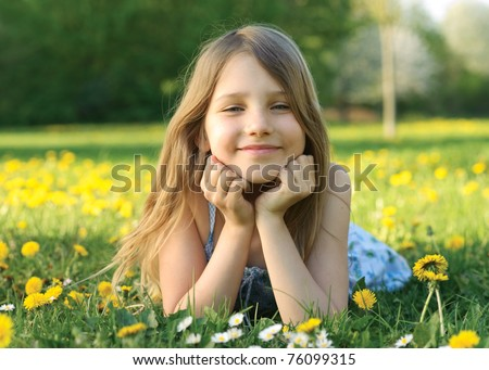 Outdoor portrait of little girl on the green grass - stock photo