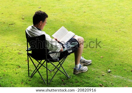 outdoor portrait of man reading - stock photo