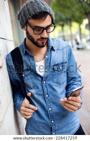Outdoor portrait of modern young man with mobile phone in the street. - stock photo