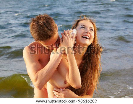outdoor portrait of muscular guy putting shell to beautiful laughing topless girl 's ear - stock photo