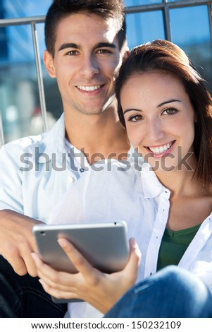 Outdoor portrait of one young couple using a digital tablet - stock photo
