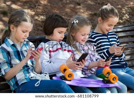 Outdoor portrait of ordinary kids playing with phones