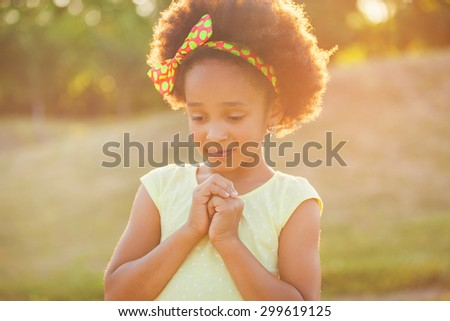 Outdoor portrait of pretty mixed race African-American girl smiling outdoor - stock photo
