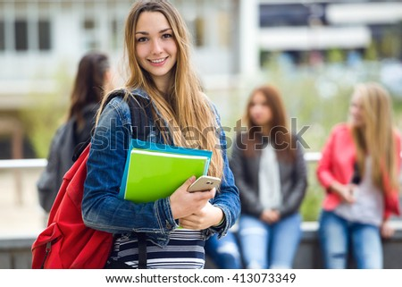 Outdoor portrait of pretty student girl in the street after class. - stock photo