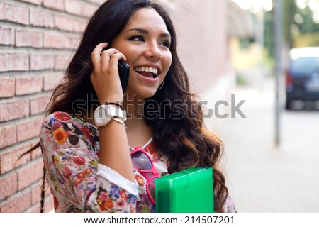 Outdoor portrait of pretty student girl talking on the phone. - stock photo