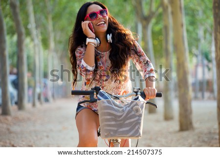 Outdoor portrait of pretty young girl riding bike and talking on the phone. - stock photo