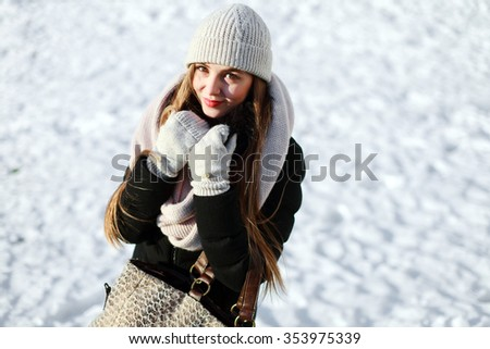 Outdoor portrait of pretty young sensual smiling woman posing on snow in winter