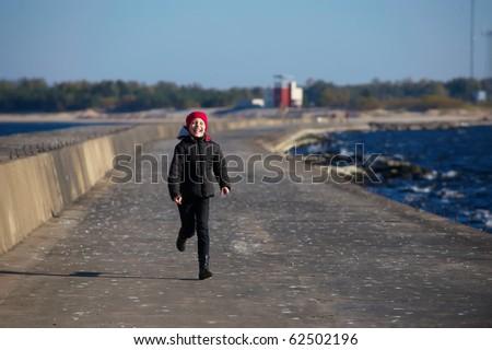 Outdoor portrait of running cheerful little girl - stock photo
