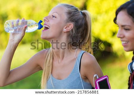 Outdoor portrait of running girl drinking water after running.  - stock photo