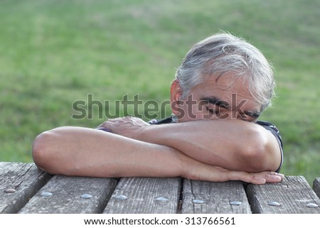 Outdoor portrait of senior man with closed eyes - stock photo