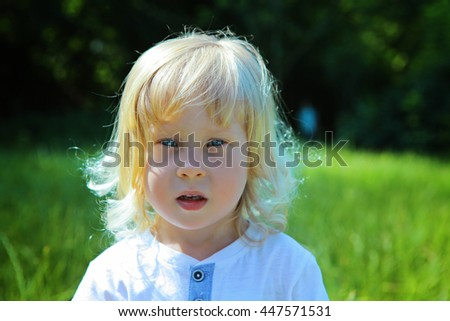Outdoor Portrait of shy cute smiling little 4-years boy with long curly blond hair. Happy five years beautiful kid  in the garden looking at camera headshot close-up - stock photo