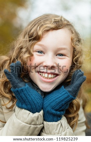 Outdoor portrait of smiling blond girl in autumn park - stock photo