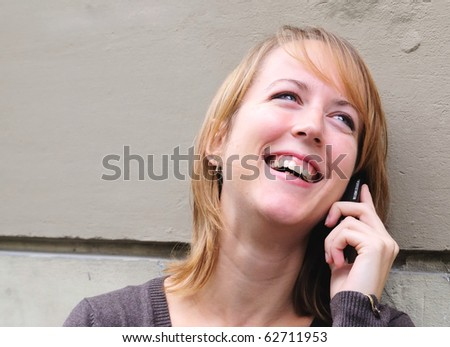 Outdoor portrait of smiling charming young woman on phone