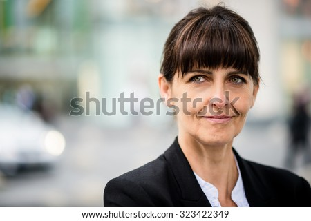 Outdoor portrait of smiling confident senior business woman looking away - stock photo
