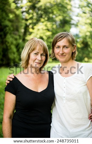 Outdoor portrait of smiling happy senior mother with her adult daughter