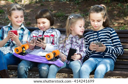Outdoor portrait of  smiling kids playing with phones - stock photo
