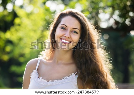 Outdoor portrait of smiling long-haired woman  - stock photo