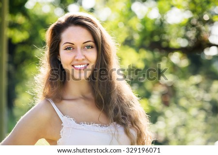 Outdoor portrait of smiling long-haired young female