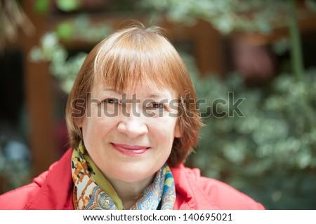 Outdoor portrait of smiling senior woman - stock photo