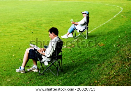 outdoor portrait of spectators in deckchairs - stock photo