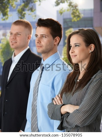 Outdoor portrait of successful and confident businesspeople standing together, smiling. - stock photo