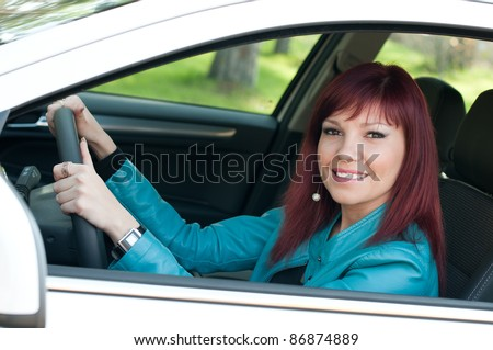 Outdoor portrait of successful cute young woman in a car - stock photo