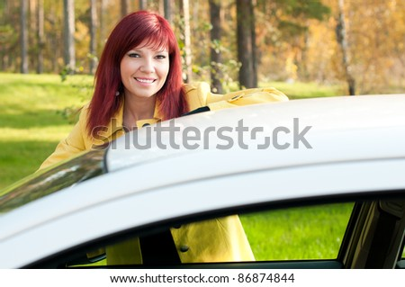 Outdoor portrait of successful cute young woman standing by her new car - stock photo