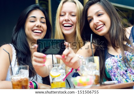 Outdoor portrait of three friends taking photos with a smartphone - stock photo