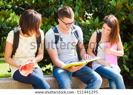 Outdoor portrait of three smiling students talking in a park - stock photo