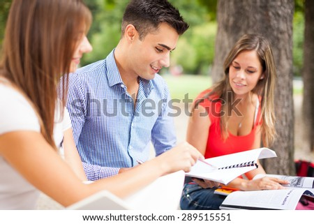 Outdoor portrait of three students studying in a park - stock photo