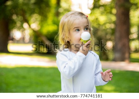Outdoor portrait of toddler  girl  with ice cream in park. Cute kid playing in the park. Happy family holidays.