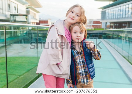 Outdoor portrait of two adorable kids in a city - stock photo