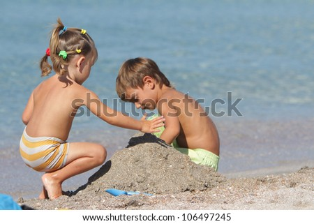 outdoor portrait of two children playing on sand beach - stock photo