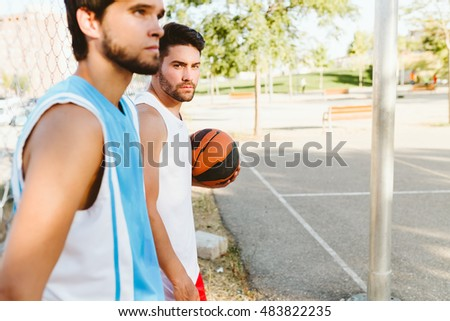 Outdoor portrait of two friends relaxing after playing basketball on court.
