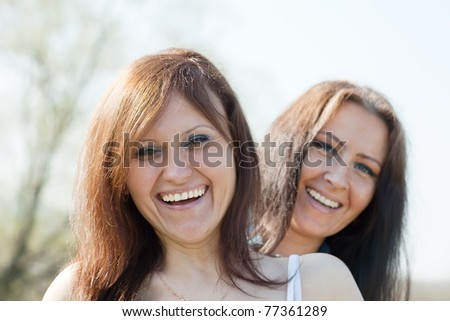 Outdoor portrait of two happy women - stock photo