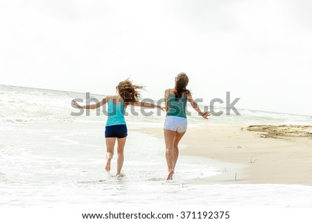 outdoor portrait of two young happy girls running away on tropical sea background, holiday image - stock photo