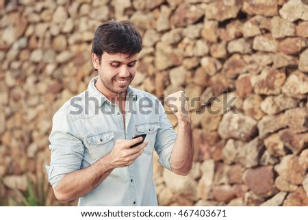 Outdoor portrait of vibrant young man with mobile phone in the street