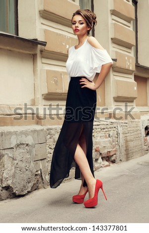 outdoor portrait of you beautiful stylish girl wearing long black skirt and white t-shirt - stock photo
