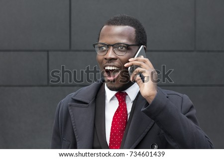 Outdoor portrait of young African male standing in street in city center dressed in formal suit, white shirt and tie, watching street, talking on phone with joyful smile, discussing business matters