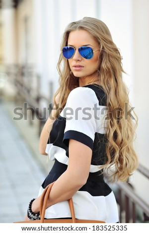 Outdoor portrait of young attractive beautiful woman with handbag wearing sunglasses - stock photo