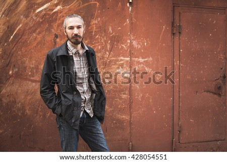 Outdoor portrait of young bearded Asian man in casual clothes over grungy garage wall background